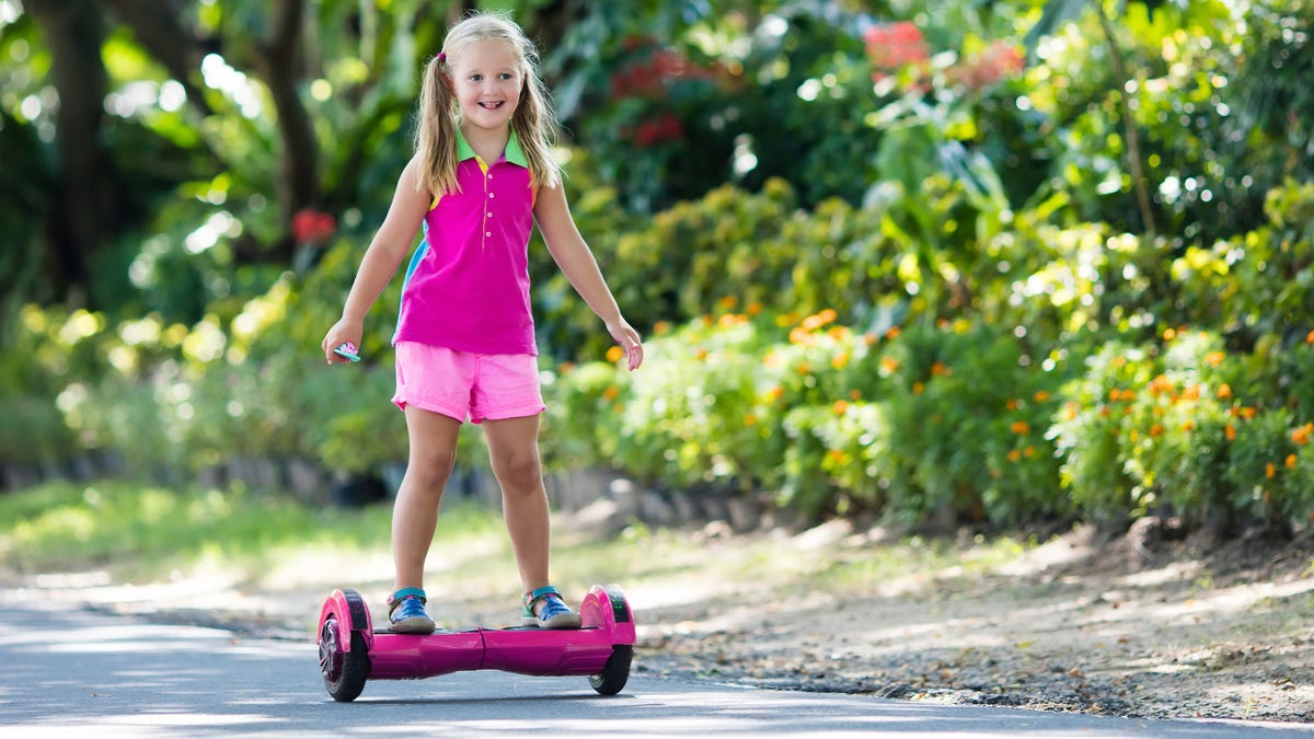 a smiling girl riding a pink hoverboard on asphalt by a garden