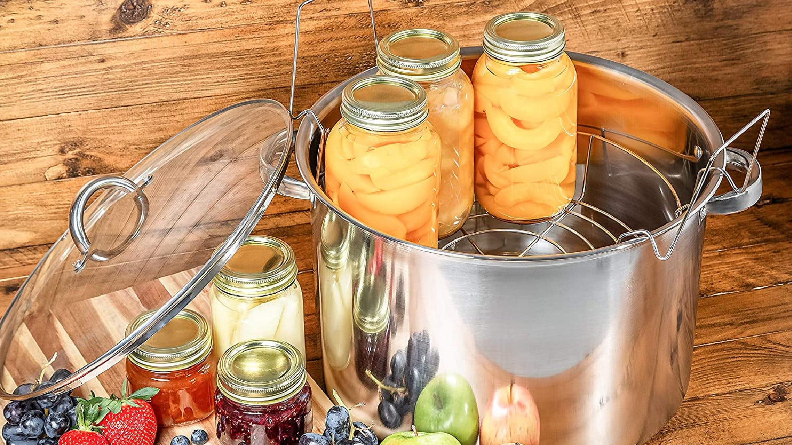 A McSunley water bath canner with jarred peaches inside with various other jarred fruits next to the canner.