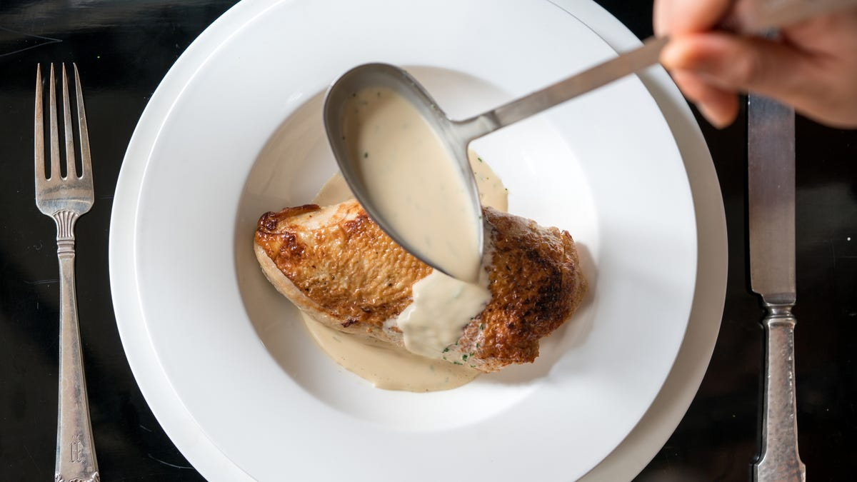 Someone pouring warm veloute sauce over a seared chicken breas with skin.
