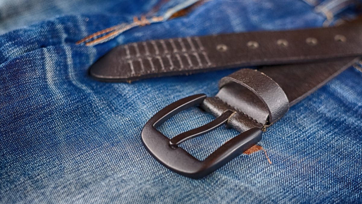 A men's leather trouser belt laying on denim shorts.