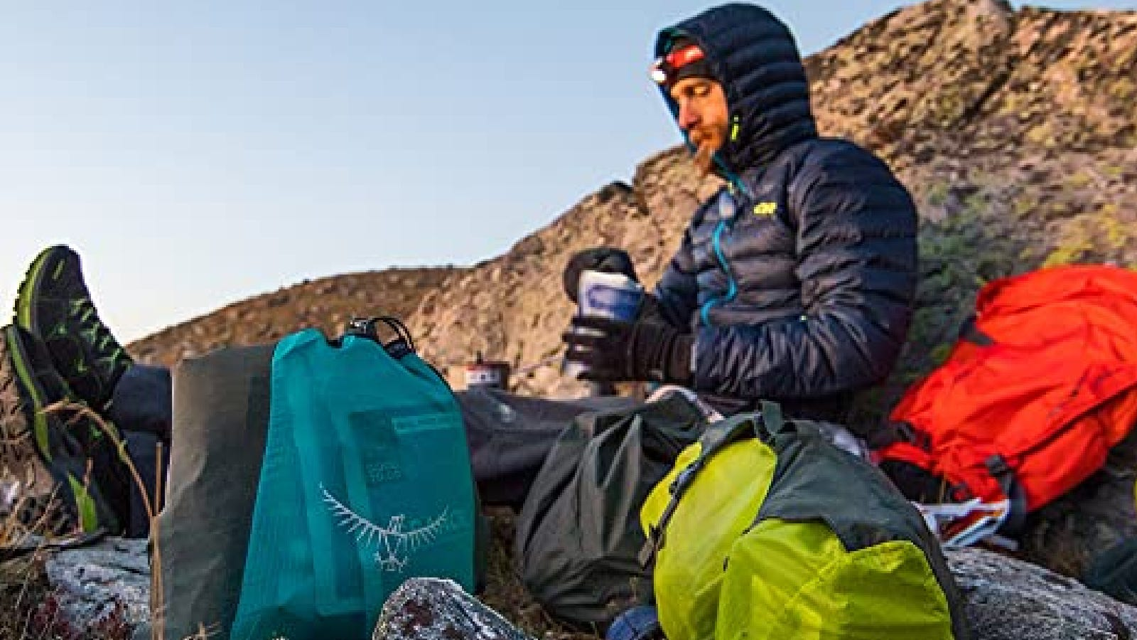 A hiker enjoying their meal on the peak of a mountain representing his osprey gear.