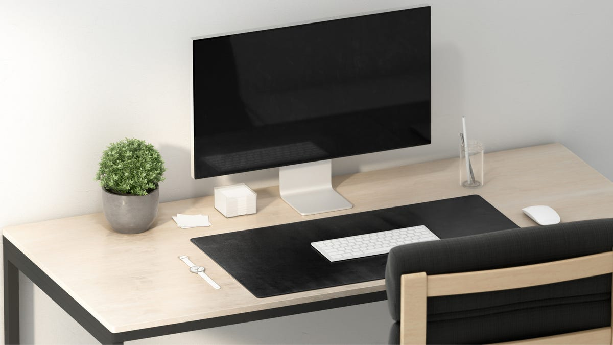 A large computer monitor and its accessories sit on a wooden desk with a black desk pad.