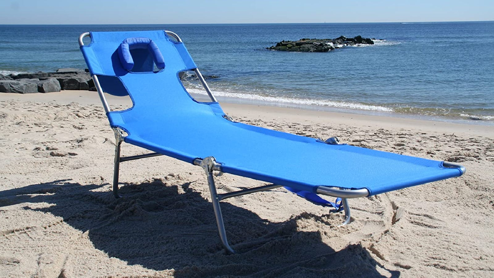 a blue chaise lounger chair with silver bars resting on the beach