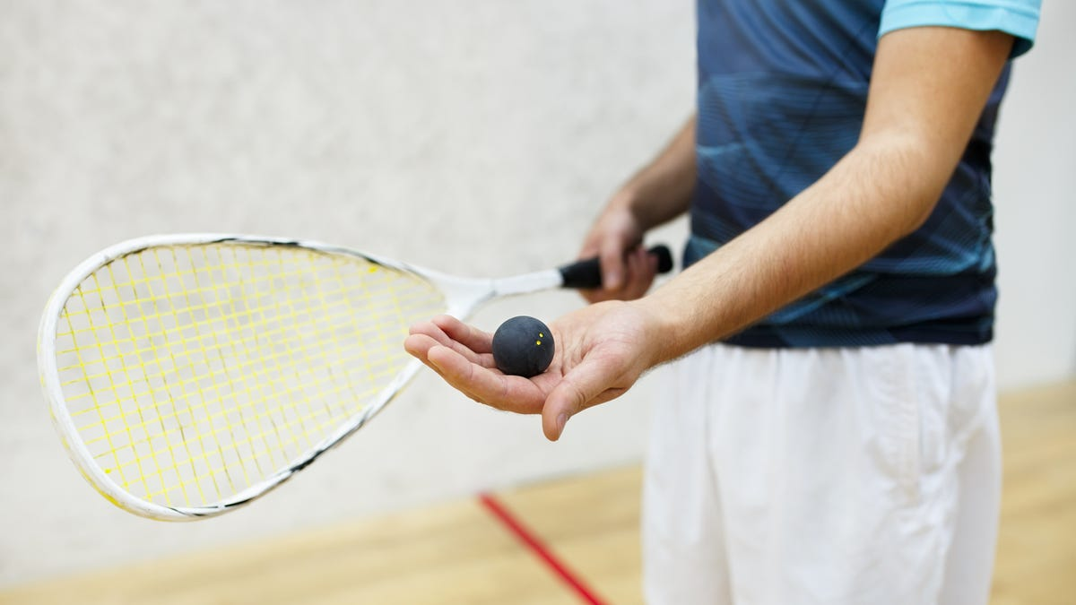 A player holding a racket and ball in an indoor racquetball court.