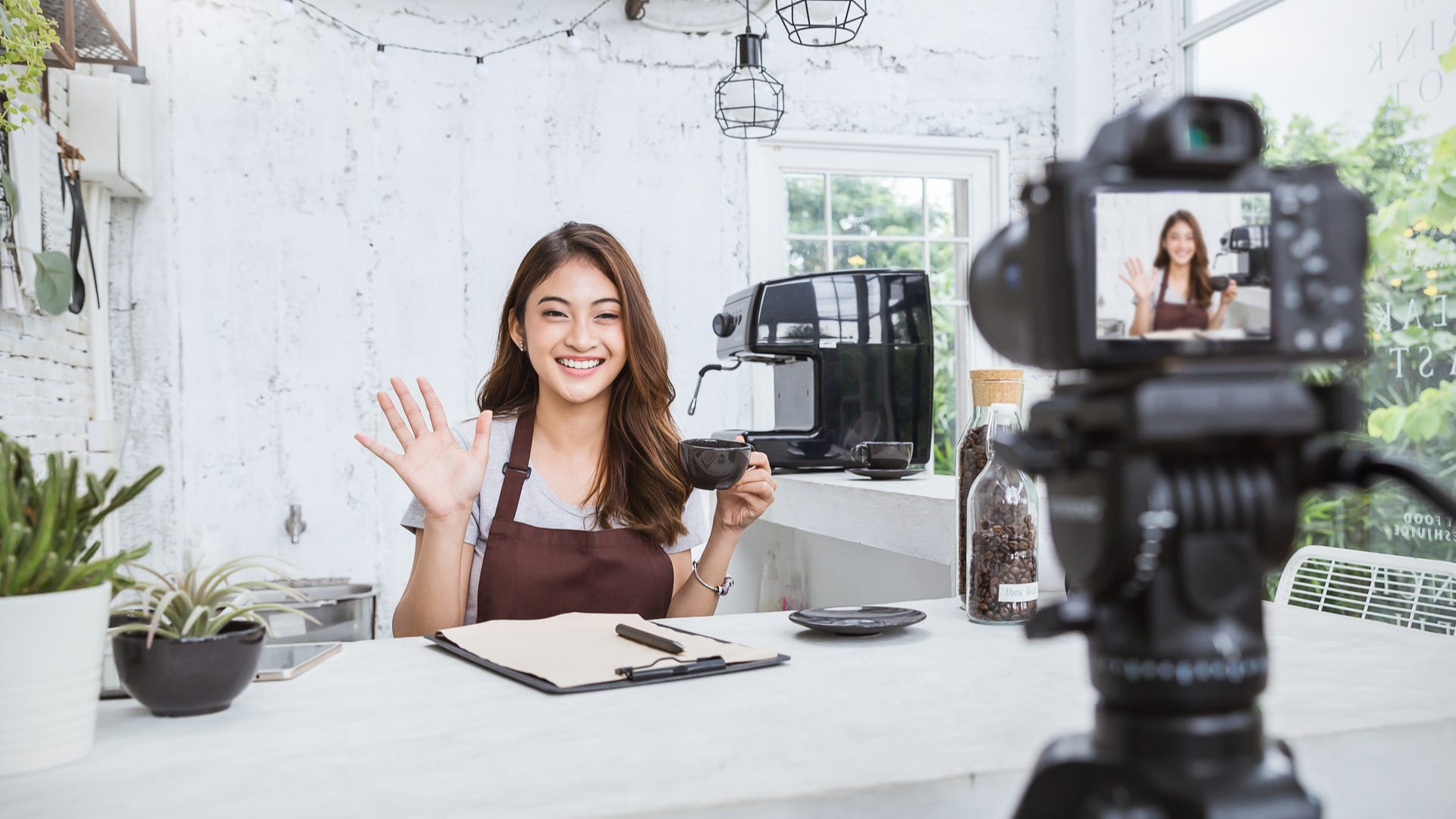 A woman films herself on a camera in a kitchen area.