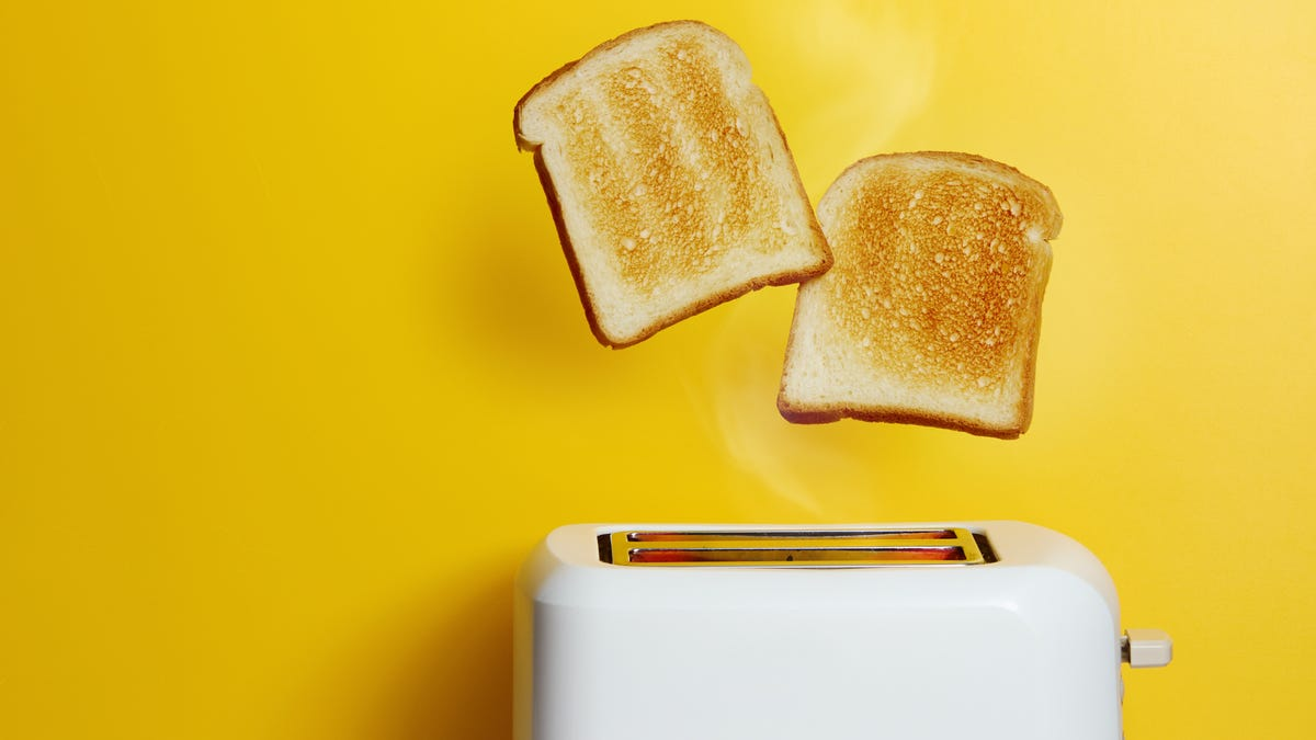Two pieces of toast pop out of a white toaster against a yellow background.