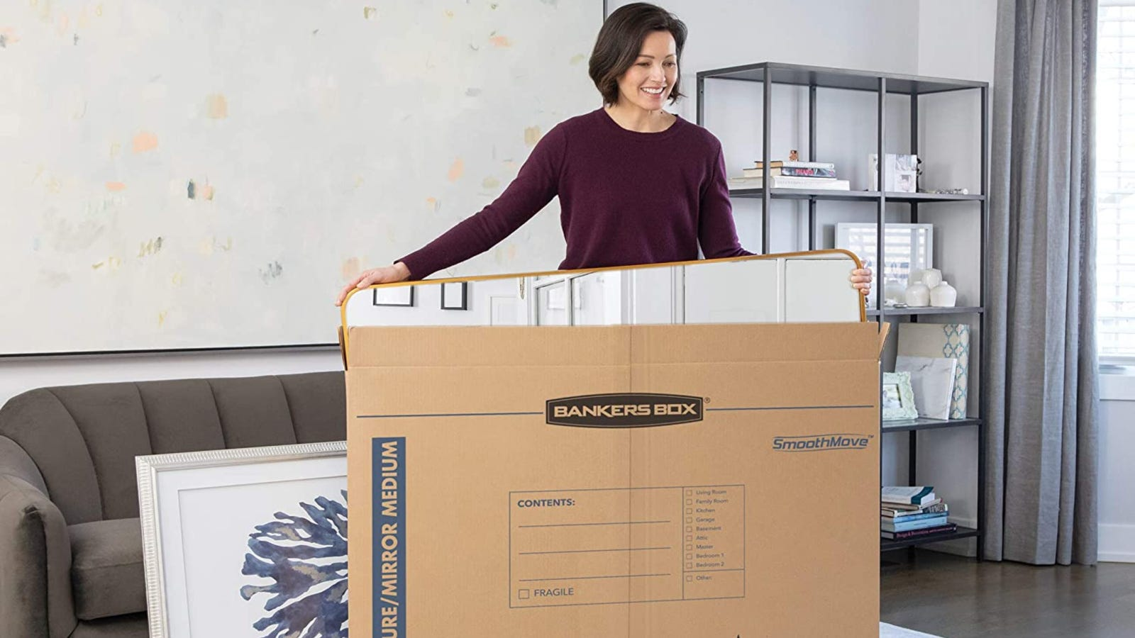 A woman placing a large mirror inside of a Bankers Box mirror box while packing other belongings too.