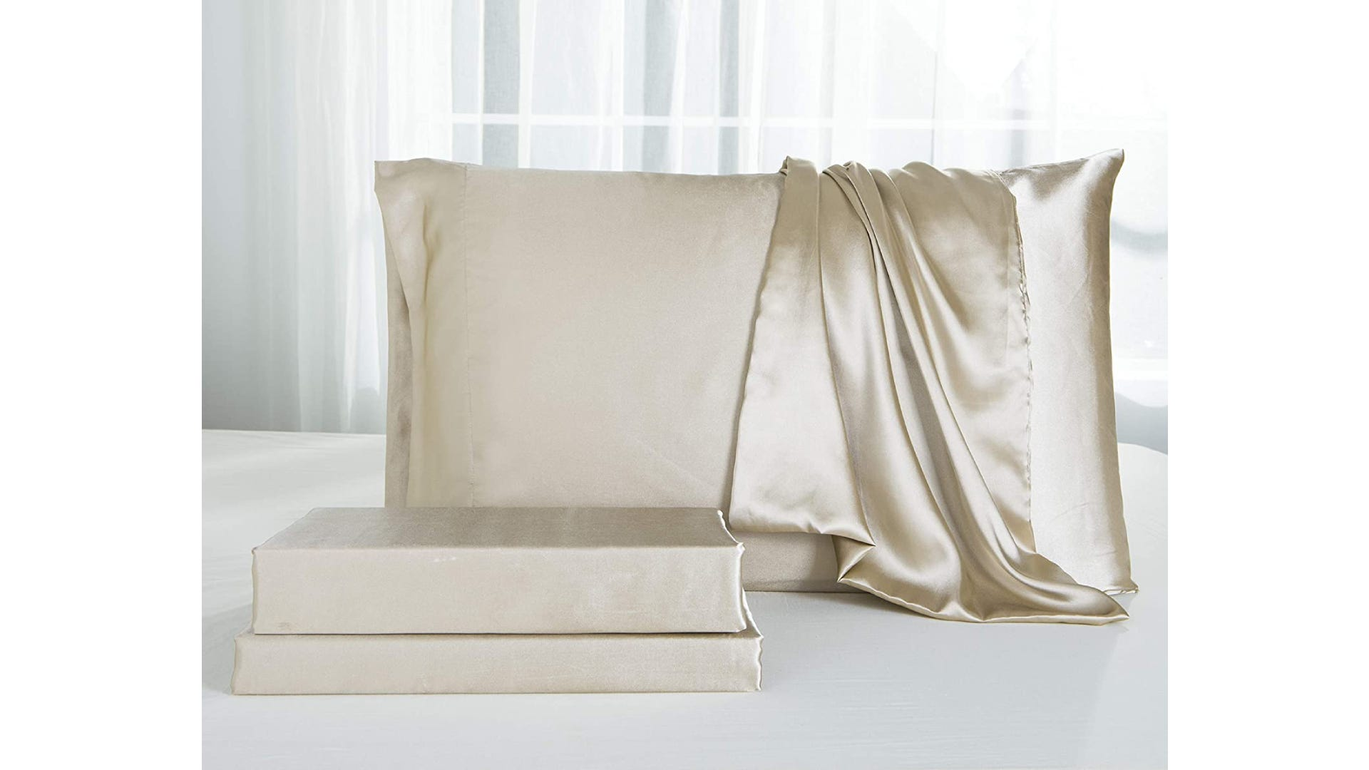 taupe colored sheet set with pillow and brand box on bed