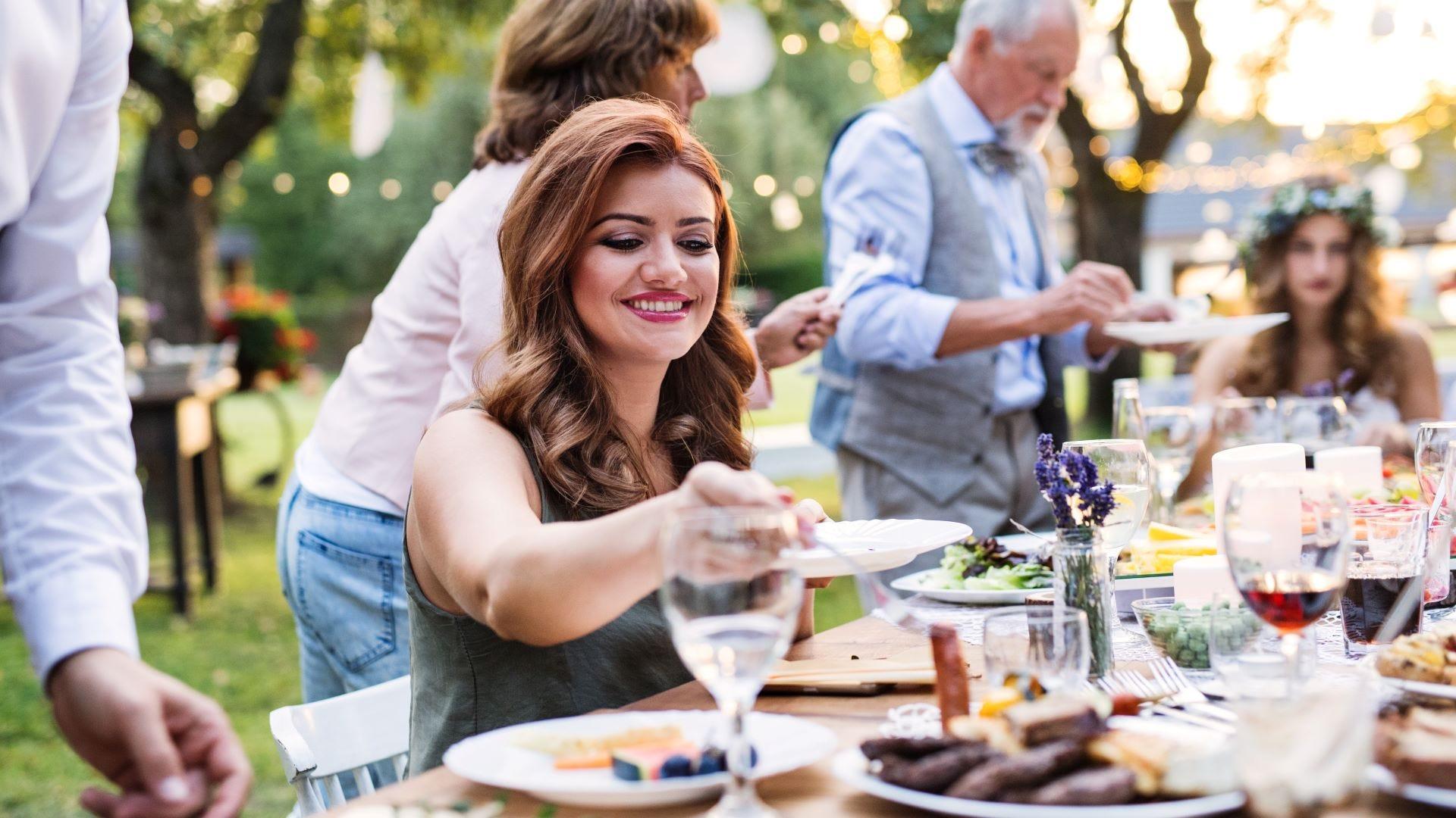 People enjoying an outdoor wedding dinner.