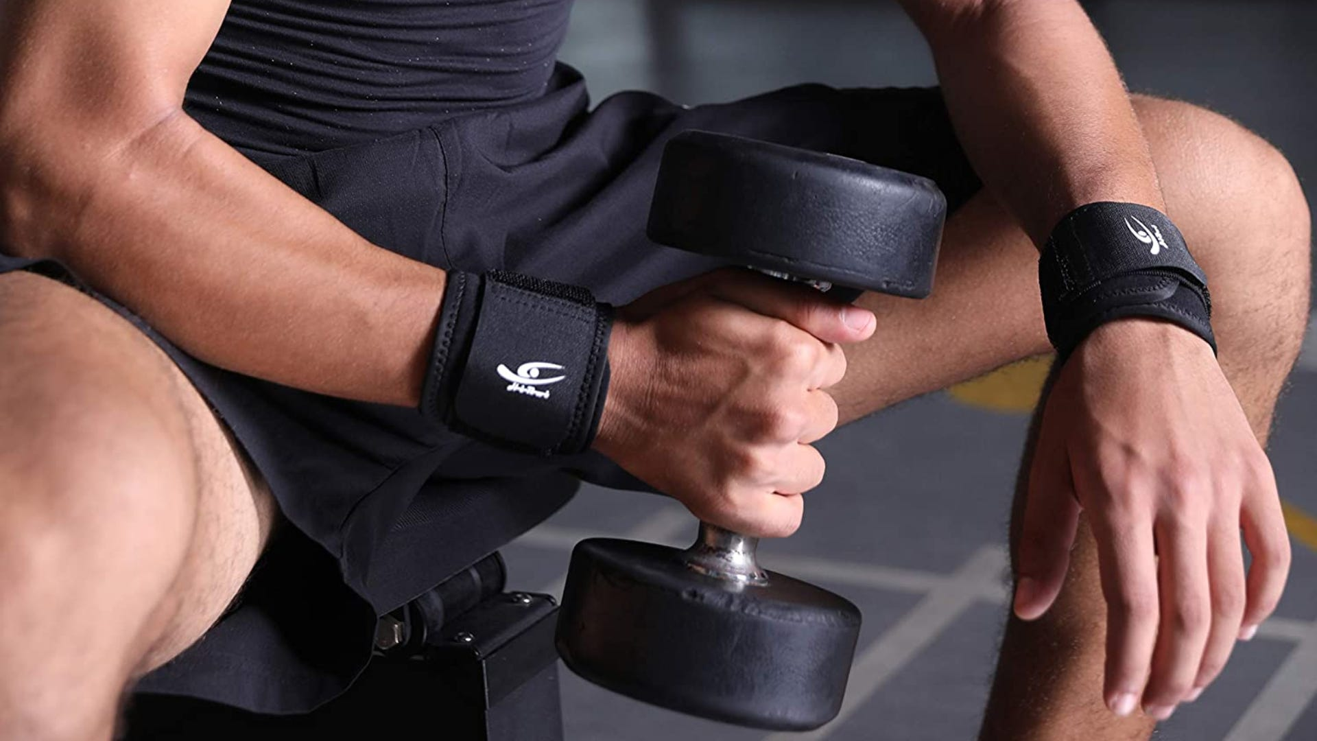 A man wearing two black wrist braces while lifting a dumbell.