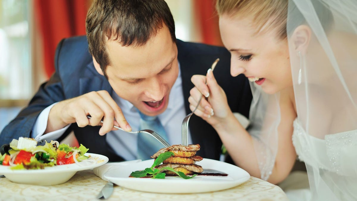A bride and groom eating a wedding dinner.