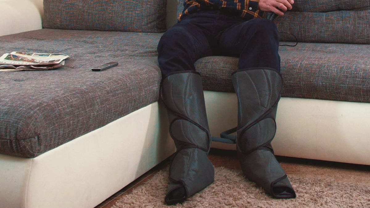 A person wearing black wrap-around calf massager while relaxing on a couch.
