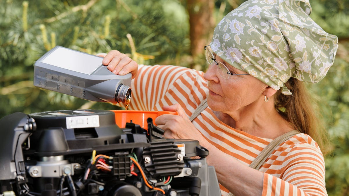 Senior woman pours oil into an outboard engine through a funnel.