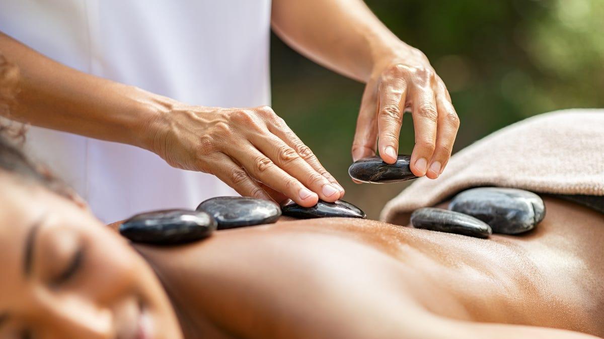 Closeup of masseuse hands placing hot stones on woman back at resort