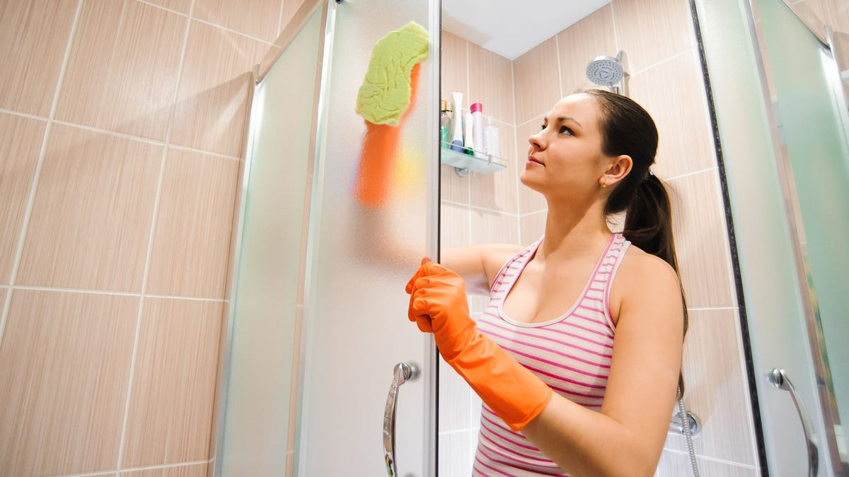 A woman wiping down a shower stall.