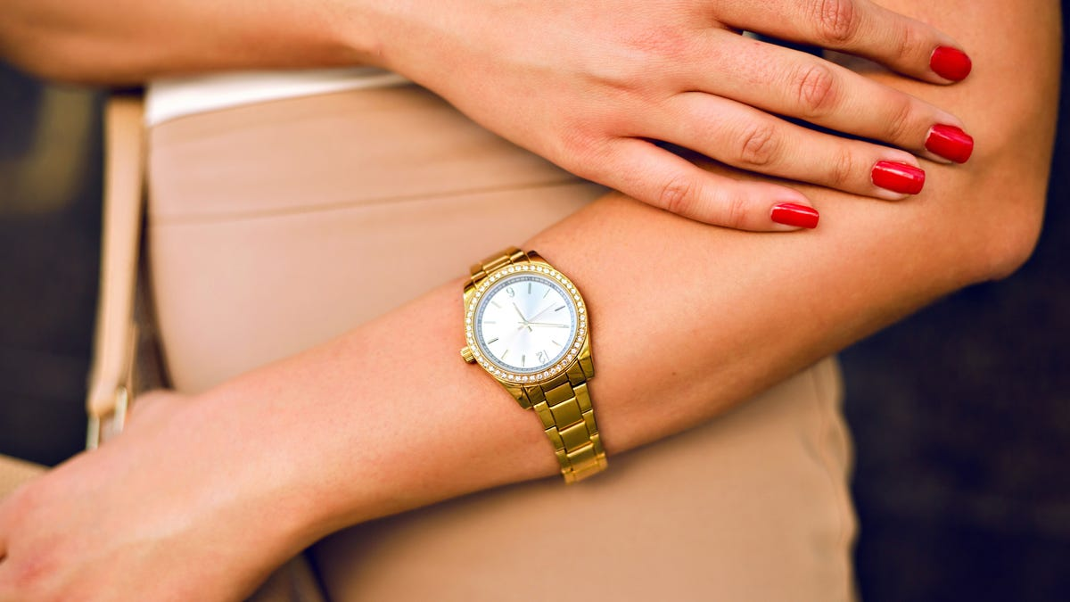 closeup of a woman wearing a gold watch with red painted nails