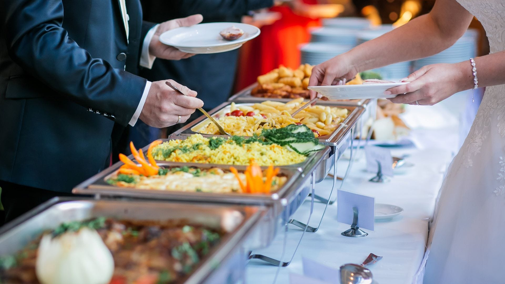 People loading plates at a buffet.
