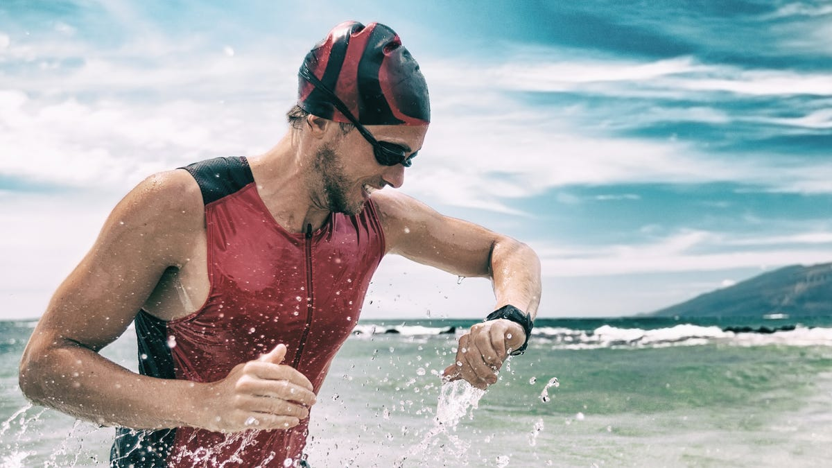 a man getting out of the water from swimming checking his sports watch