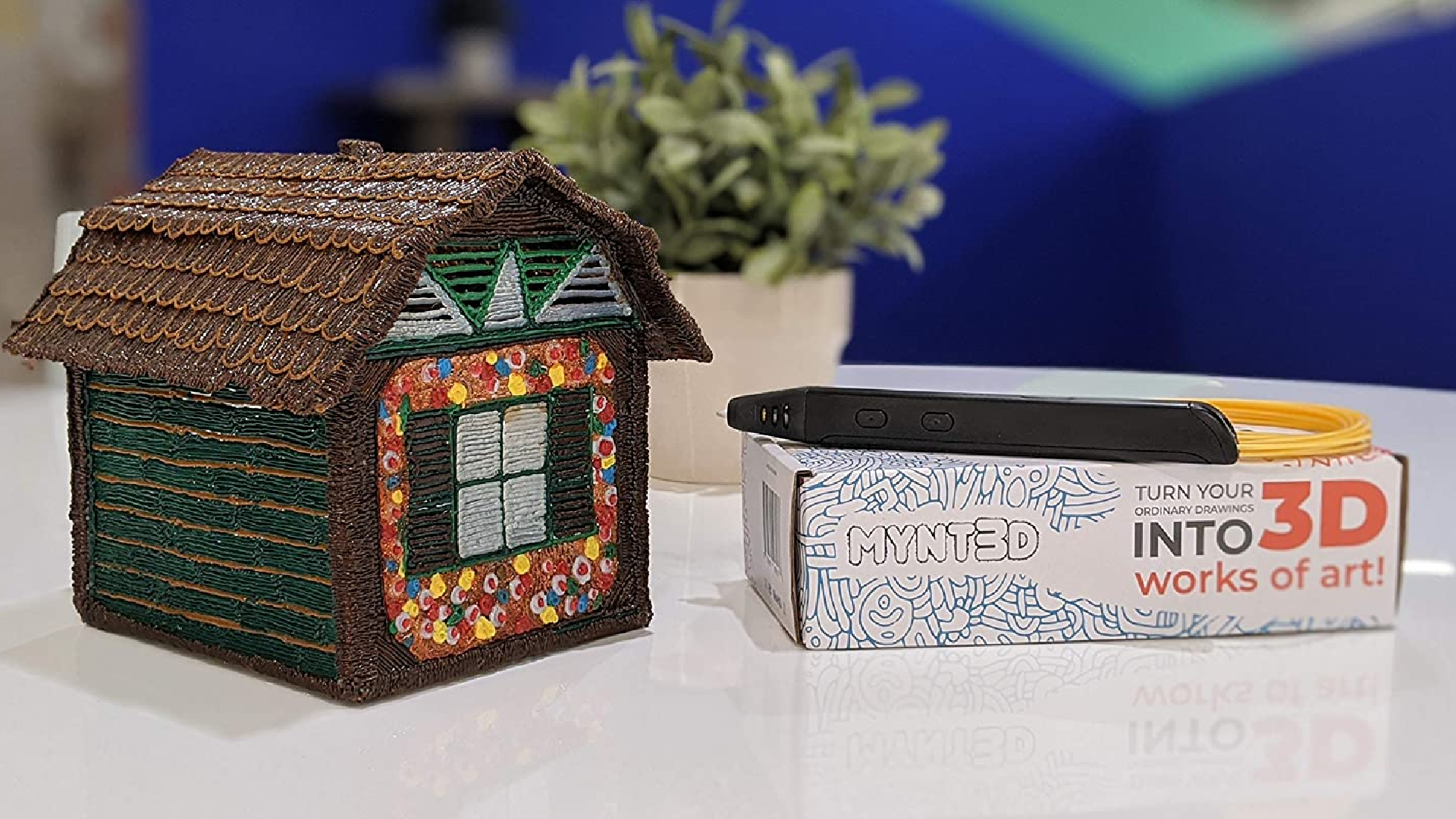 a house drawn with a 3D pen and the box with stylus on top of it