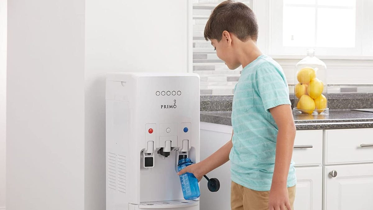 A young boy filling a blue water bottle from the cold spout of a white water cooler.