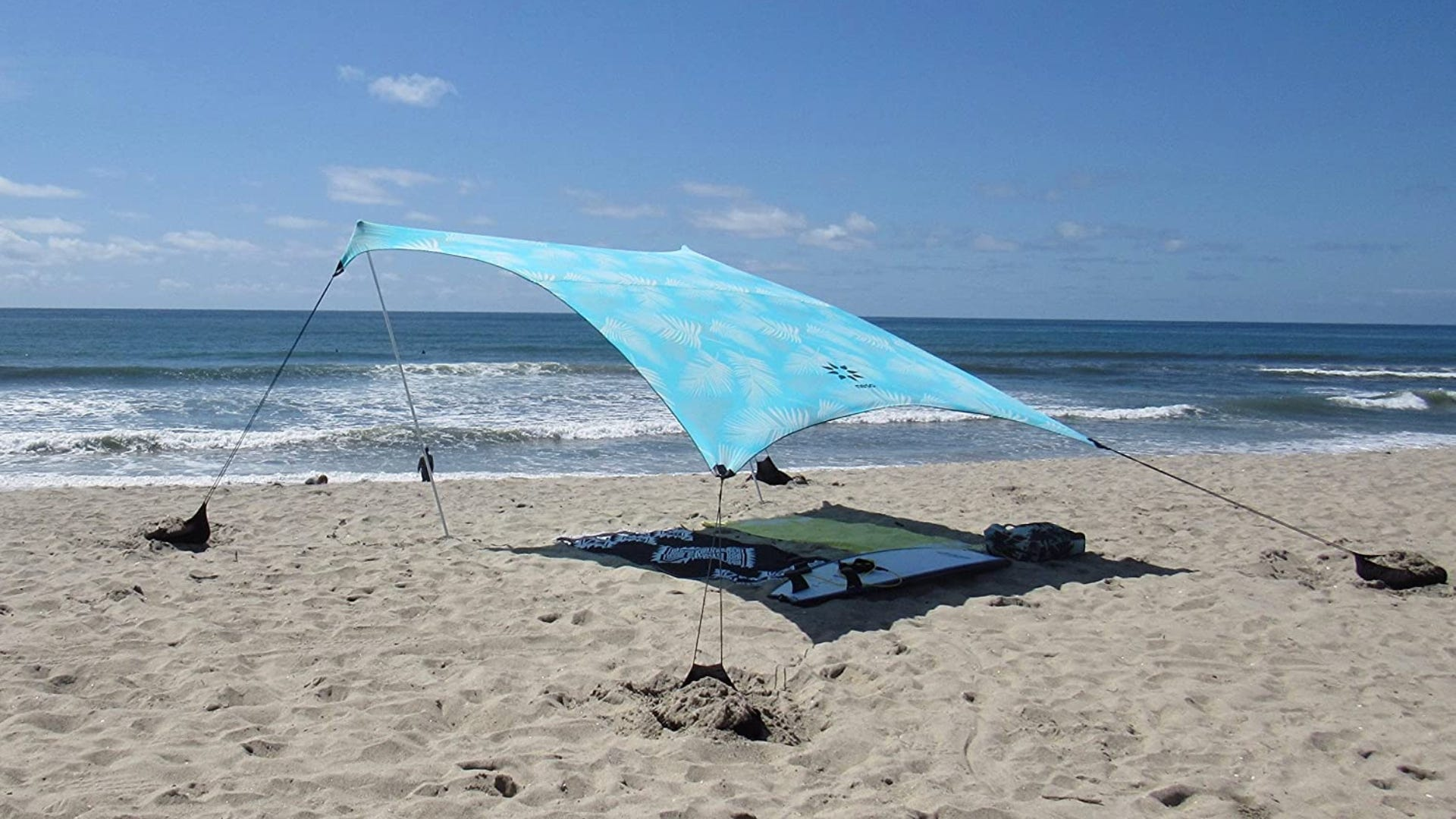 A aqua colored canopy spread over towels on a beach.
