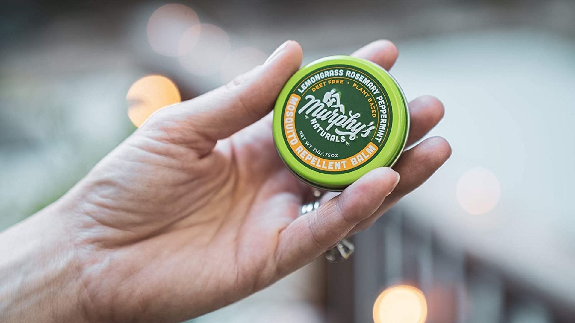 Someone holds a round container of bug repellent balm