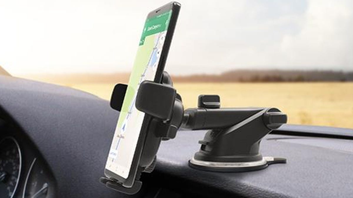 A dashboard car phone mount with phone showing directions in car.