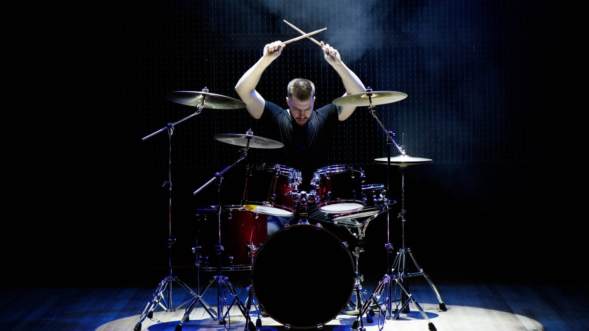 a man drumming on a drumset on stage with a spotlight on him