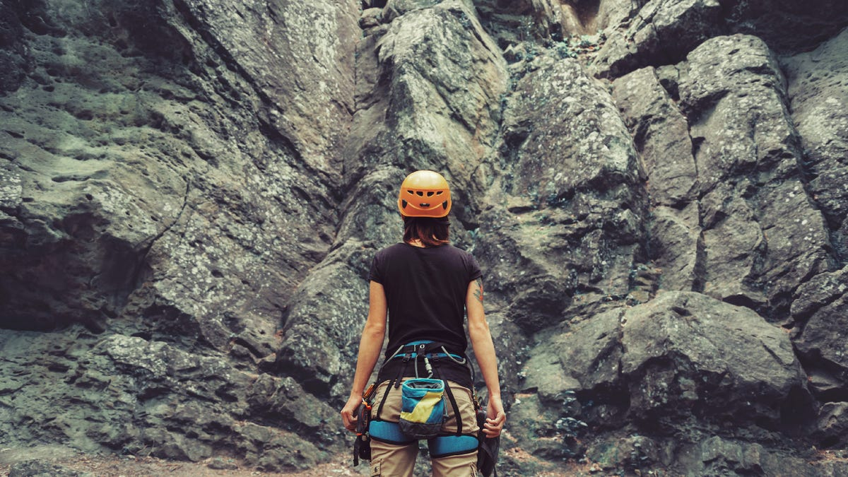 Young woman wearing climbing harness and helmet standing in front of a rock wall outdoors and preparing to climb