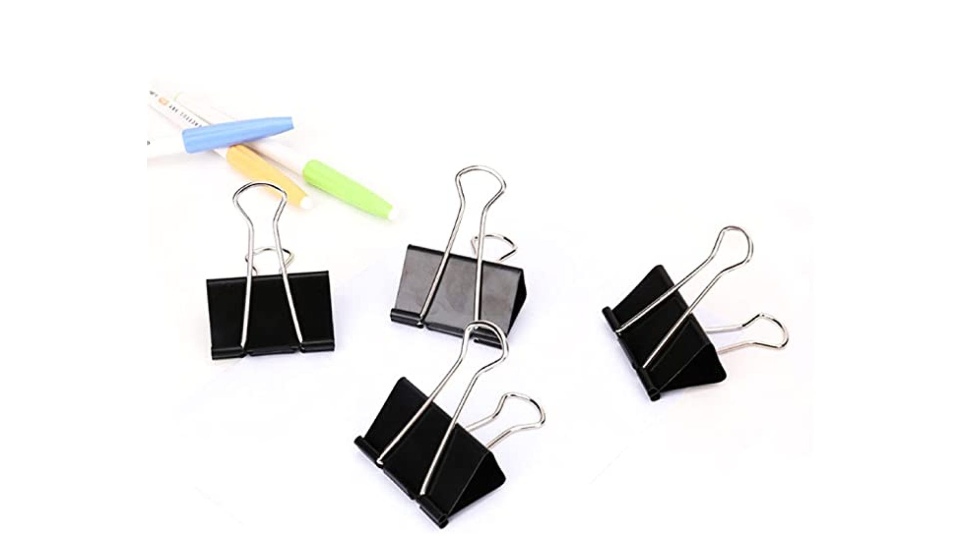 four large black binder clips displayed by pens