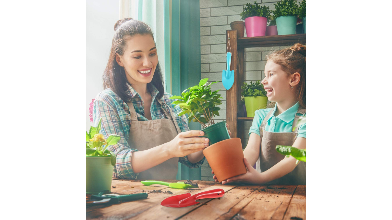 Woman and girl at a table, potting a flower with trowels.