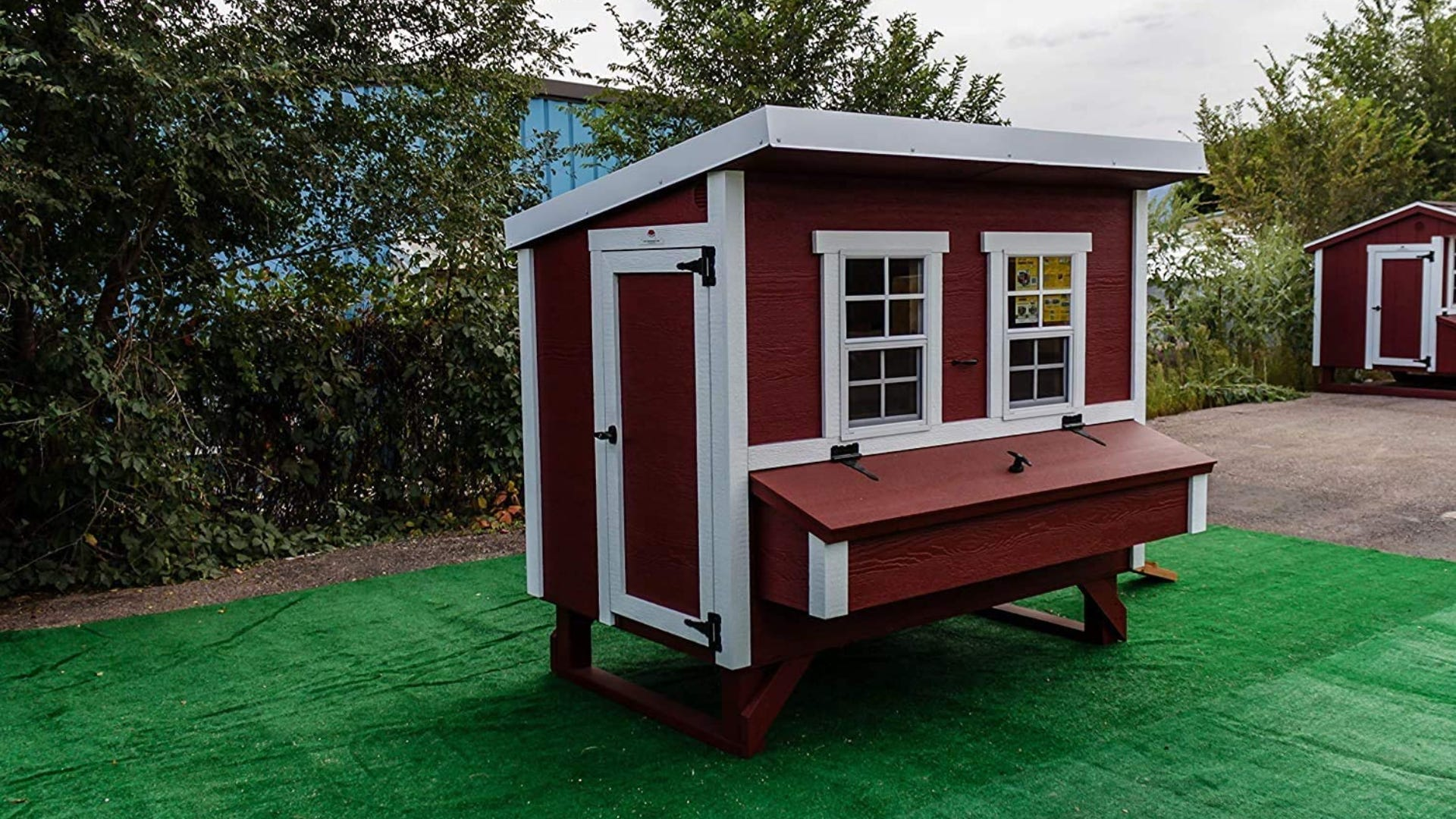 Red painted wooden coop with white trim sitting in a grassy area.