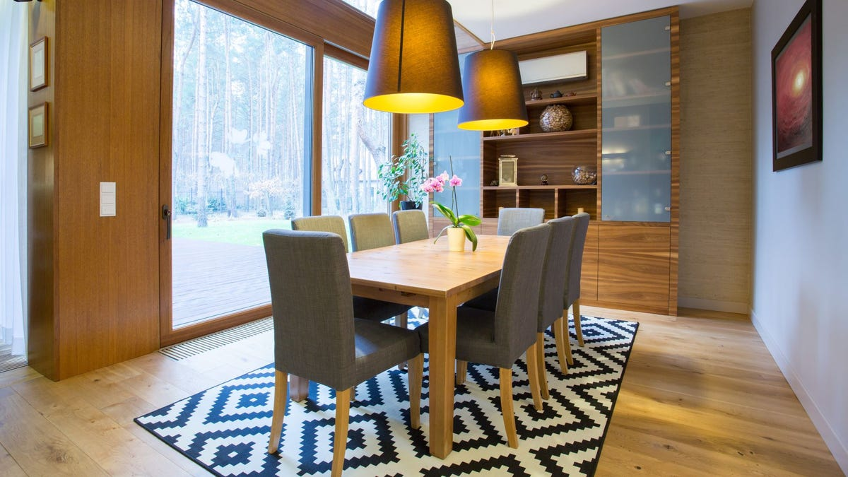 A modern wooden dining set on a black and white area rug with a diamond design.