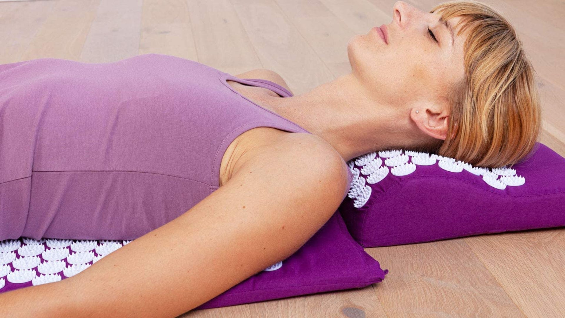 A side view of a woman laying on a purple acupressure mat.