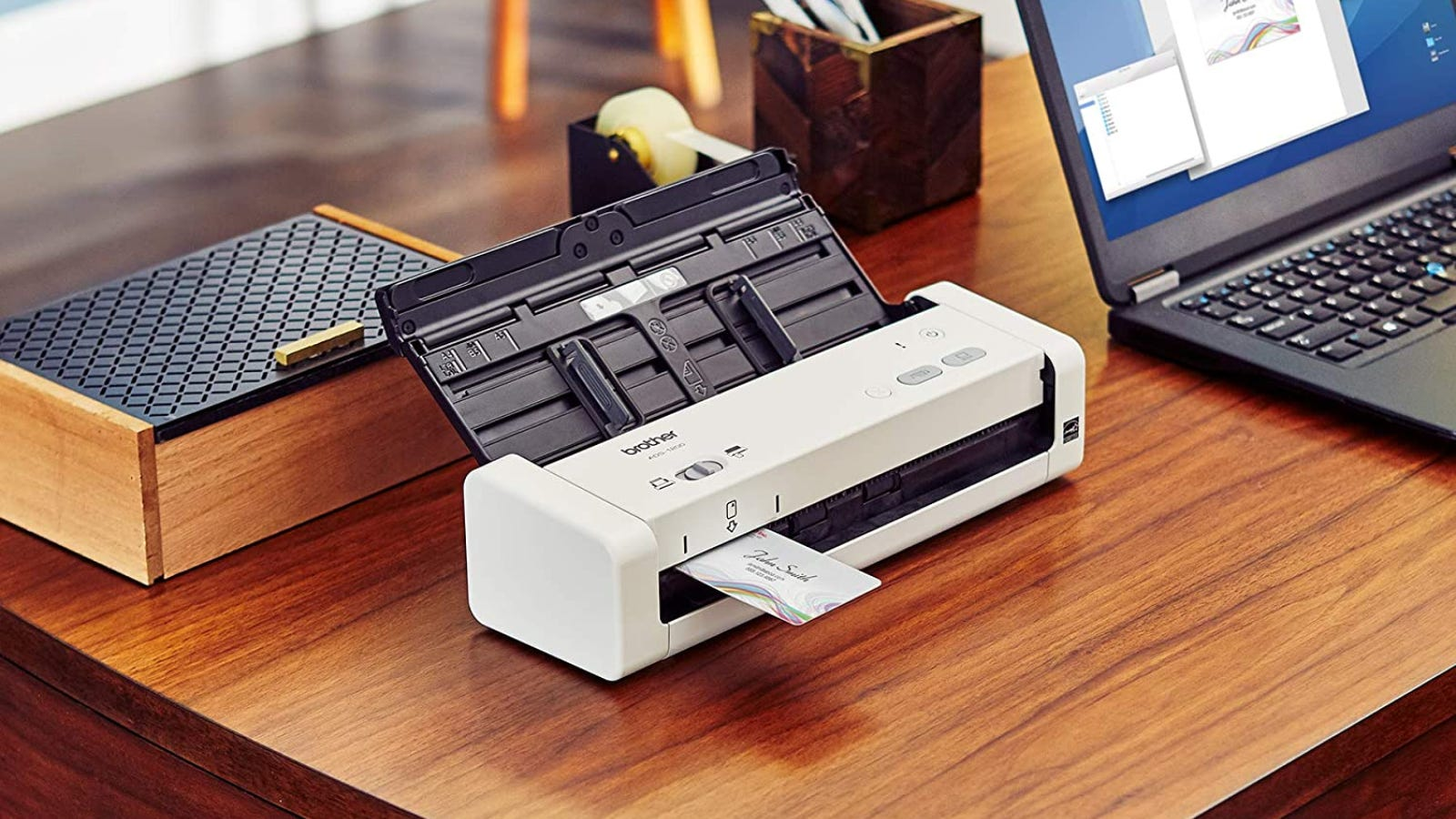 A document scanner sitting on a wooden desk next to a laptop.