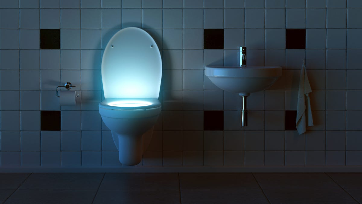 a toilet in a dark bathroom with light coming from the toilet bowl