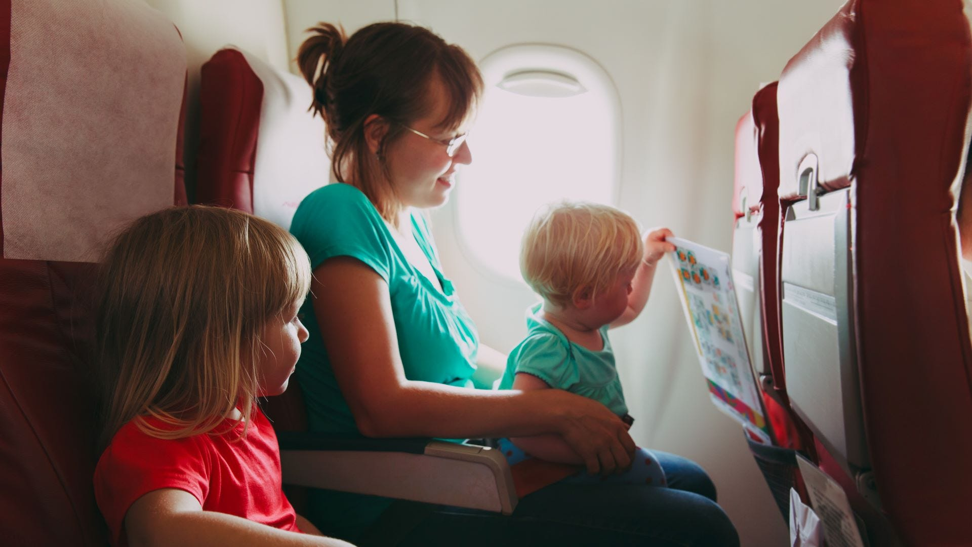 A woman on a plane holding a toddler with an older child in the seat next to her.