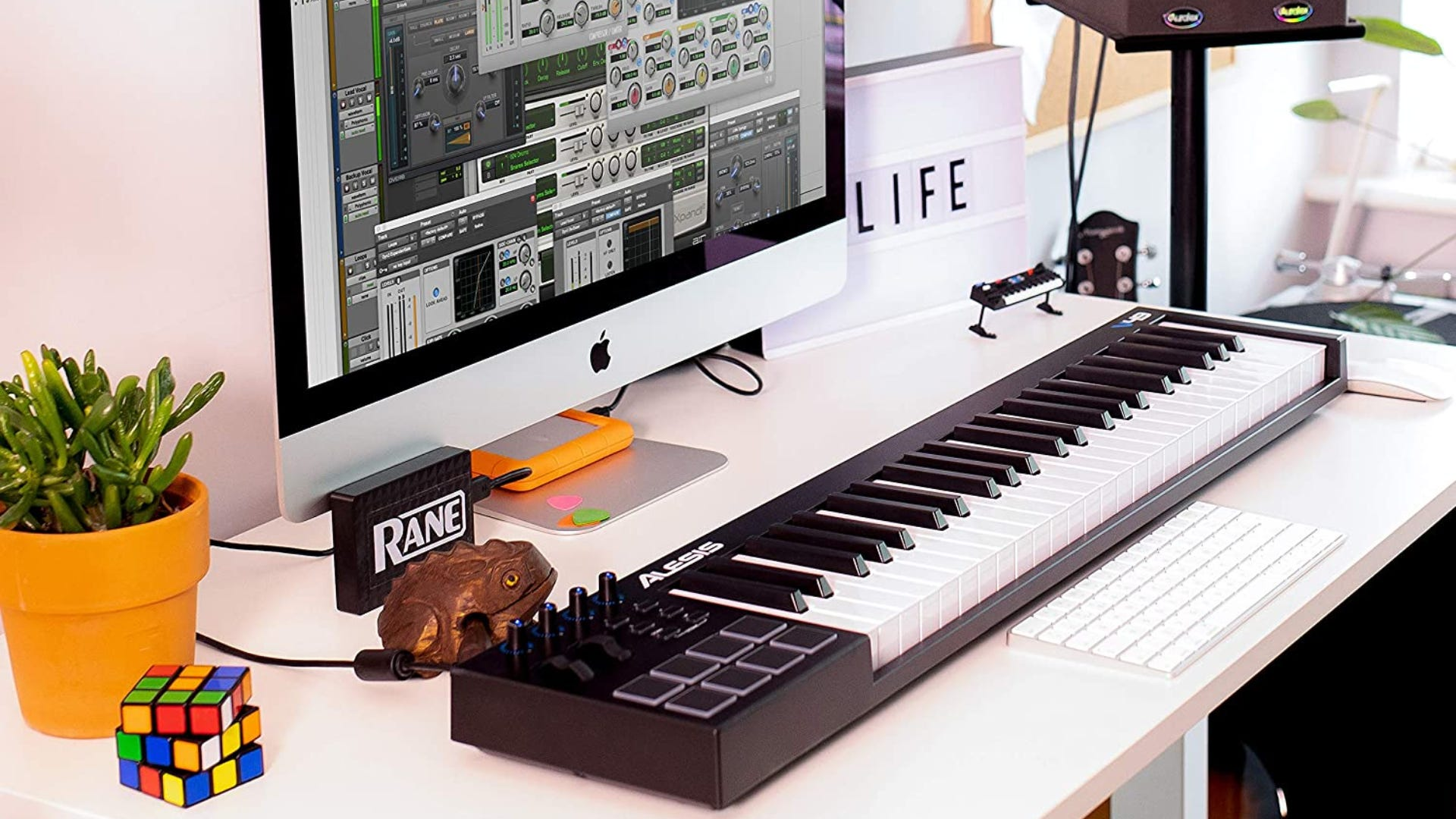 A MIDI keyboard sitting on a decorated desk with a computer.