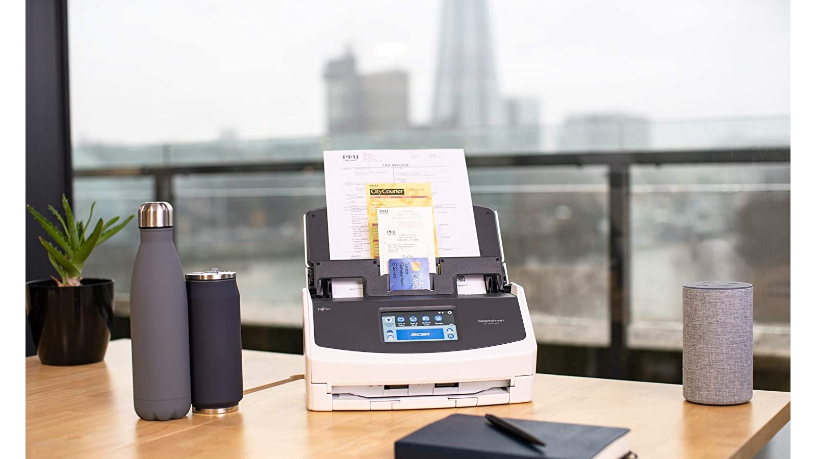 A white and black document scanner sitting on a wooden desk next to a notebook and water bottles.