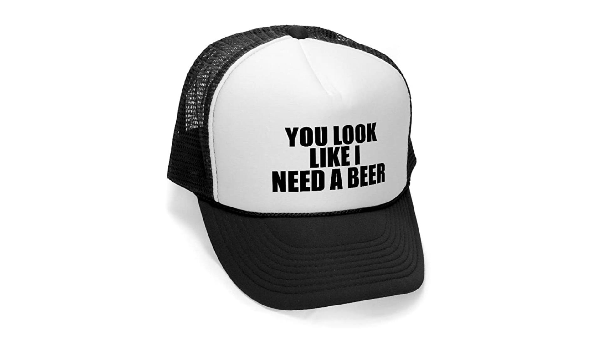 """A white and black hat that says """"You Look Like I Need A Beer"""" on the front."""