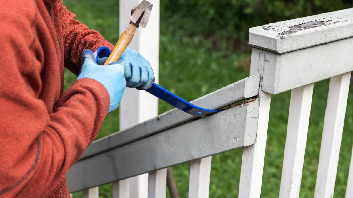 Man using a hammer and blue pry bar to tear down an old deck railing.