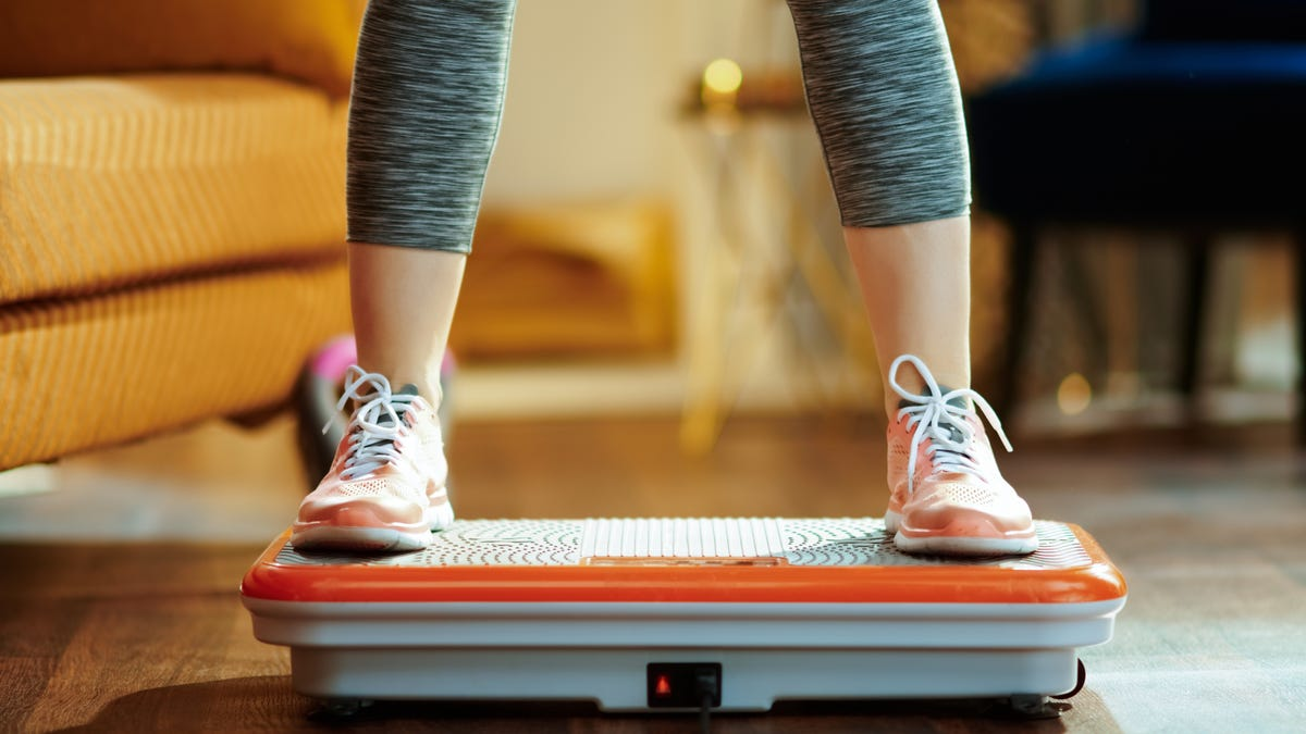 a woman in workout clothing standing on a vibration plate machine in her living room