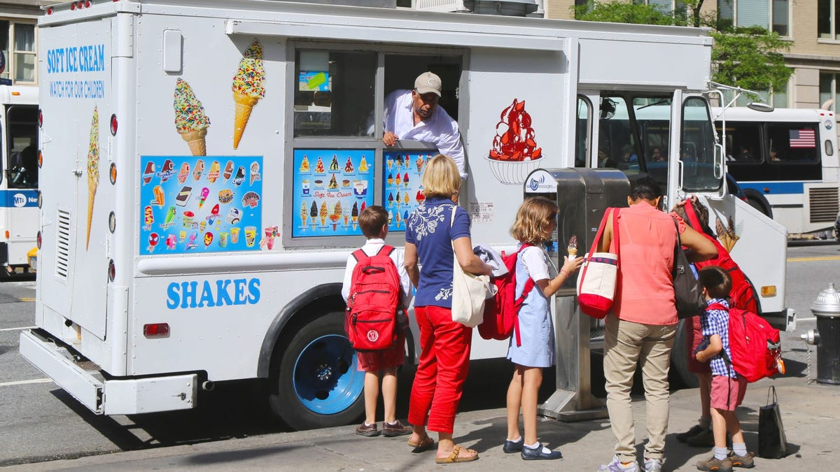 A group of kids waiting in line at an ice cream truck.