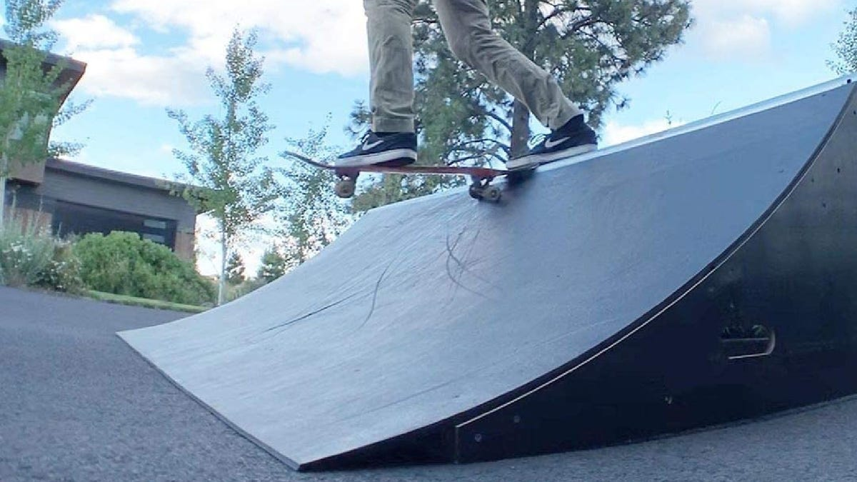 a skater on a ramp in a driveway