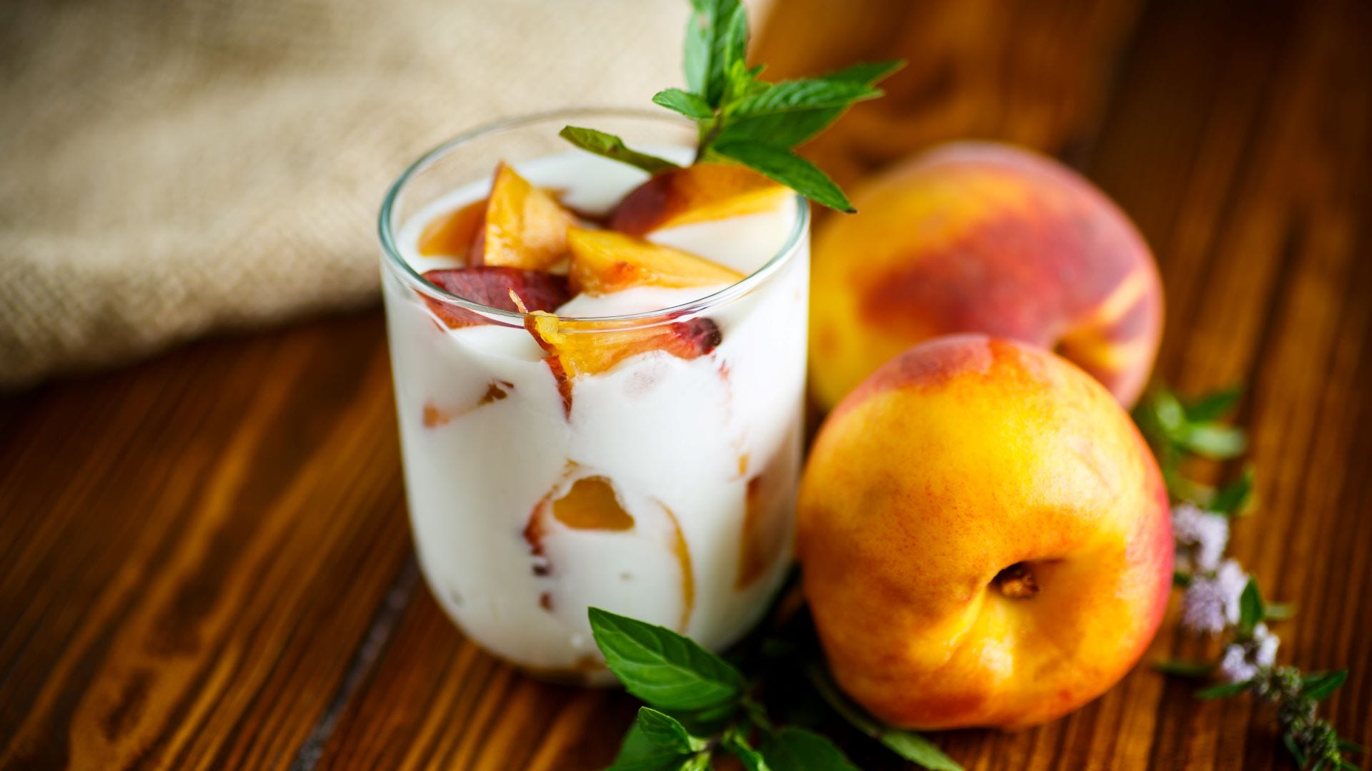 Yogurt and sliced peaches in a glass cup with two peaches next to it.