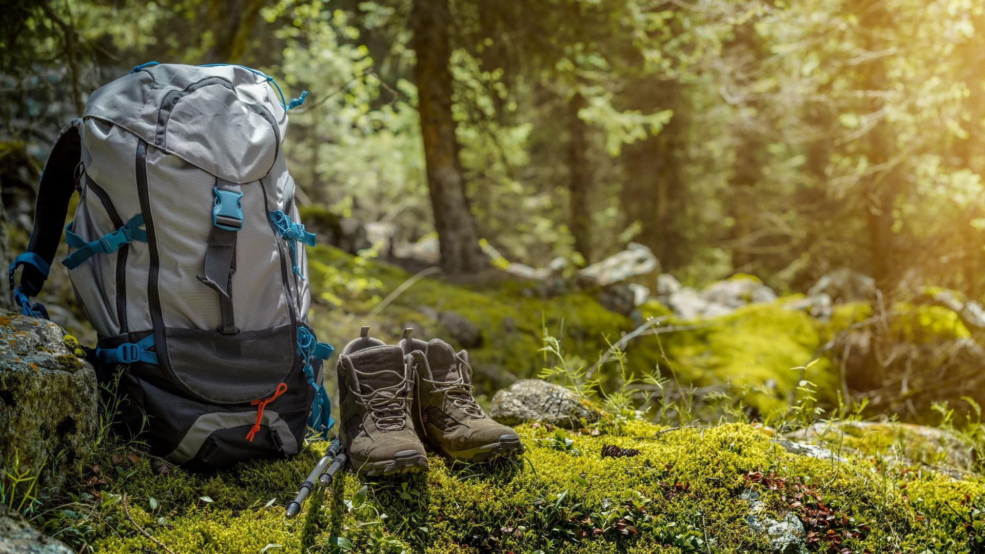 A hiking backpack next to a pair of hiking boots.