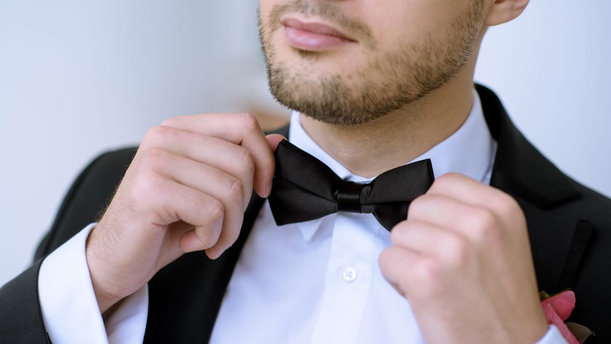 Close-up of a man in a tuxedo straightening his black bow tie.
