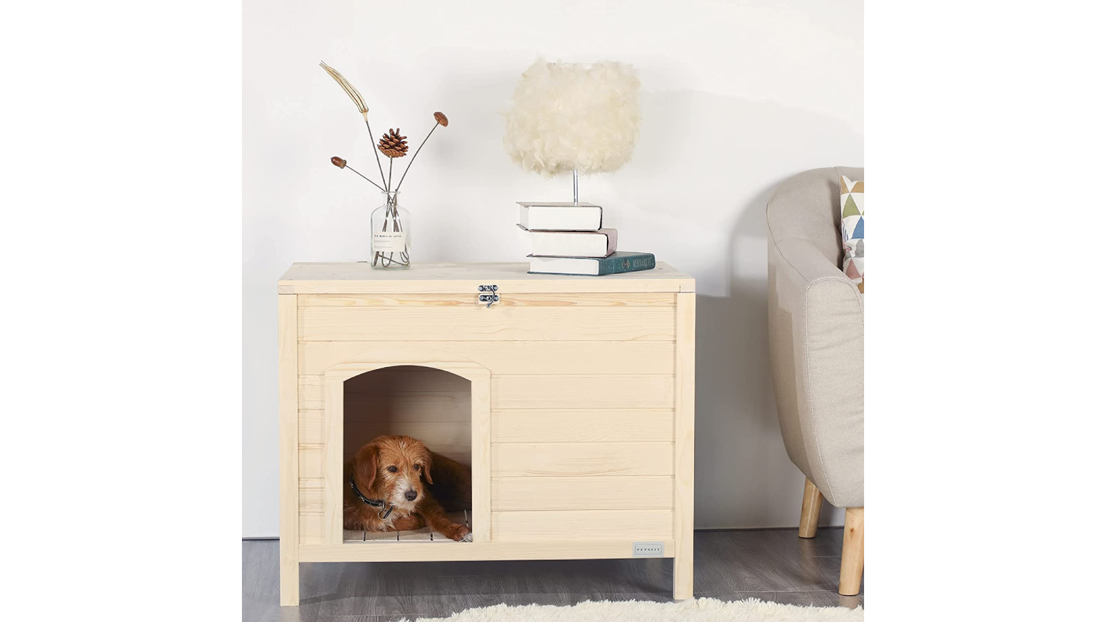 White wooden indoor doghouse with dog peeking out the door.