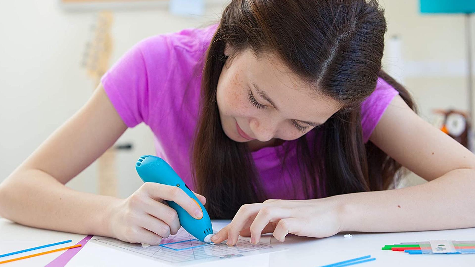 a girl using a 3D pen