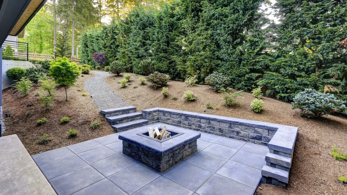 A firepit in the middle of a stone patio.